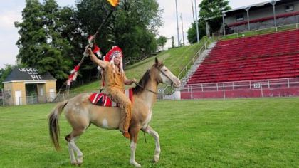 The Quips' mascot, waving his flaming spear, rides his horse on the field at Carl Aschman Stadium in Aliquippa.