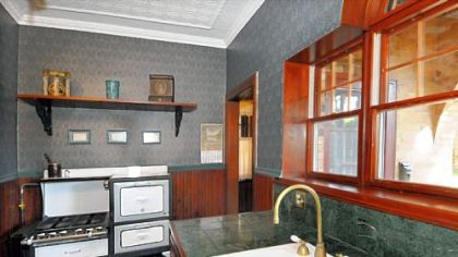 The kitchen features updated wooden cabinets and marble countertops.