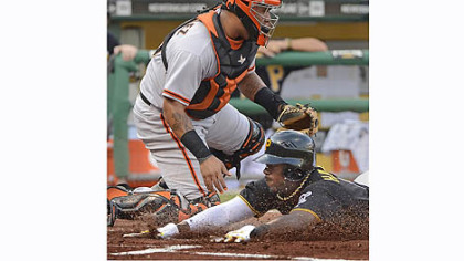 The Pirates' Josh Harrison beats a throw home in front of Giants catcher Hector Sanchez Friday night at PNC Park.