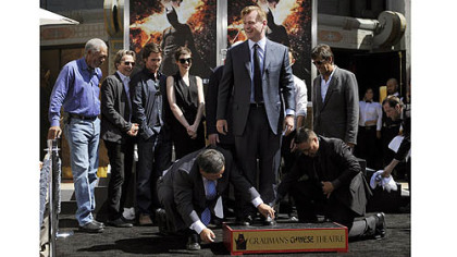 Christopher Nolan, center, director of the  film &quot;The Dark Knight Rises,&quot; is surrounded by cast members from the film as he takes part in his hand and footprint ceremony at Grauman&#039;s Chinese Theatre on Saturday.