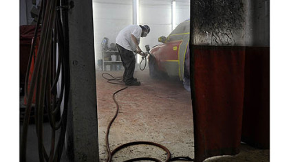 William Lieberth Sr. says he wants to leave the shop to his son, Bill Lieberth, 34, pictured above painting a Hyundai Elantra on Monday.