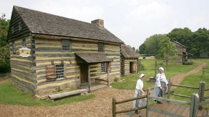 Tour guides Zoe Johnson, left, and Kaitlin Davis walk from the cabin that re-creates a tavern and courtroom from the era of  the American Revolutionary War in Historic Hanna's Town.