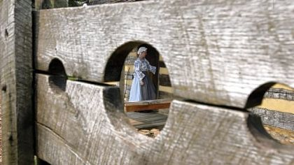 Tour guide Kaitlin Davis is seen through a hole in the pillory at Historic Hanna's Town.