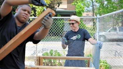 Stefan Lessard, the bassist for the Dave Matthews Band, right, works alongside Jaymier Scarbrough, 15, of Wilkinsburg at the Homewood-Brushton YMCA's community garden.