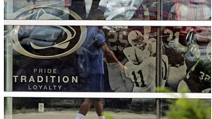 A student is reflected in the window of the Mildred and Louis Lasch Football Building on Penn State's main campus in State College.