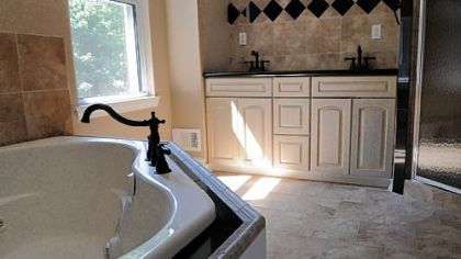 The master bathroom features a corner whirlpool tub, double-vanity sinks, ceramic tile and a separate shower that has a built-in seat.