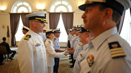 Incoming Commander Lindsay Weaver, center, shakes hands with members of her unit.