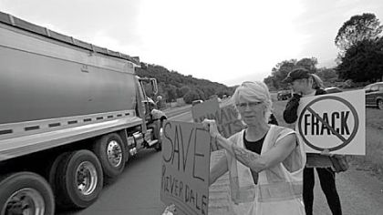 Activist Wendy Lynne Lee takes the protest to Route 220 in front of the Riverdale Park, where much of the passing truck traffic is related to natural gas well development.