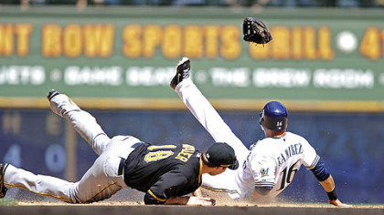 The Pirates' Neil Walker gets his glove kicked out of his hand by the Brewers' Aramis Ramirez as he steals second base during the sixth inning.