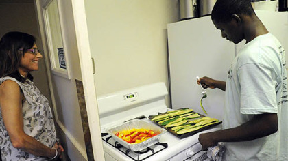 Mberwa Mada, 17, cooks zucchini while program coordinator Kate Borger looks on at Phipps Garden Center. Eight high school interns had their first cooking session June 21.