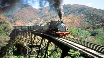 "A steam train crosses the bridge below Agua Caliente, Guatemala. This steel structure was subsequently dismantled by scrap metal thieves after the declaration of ""lesivo."""