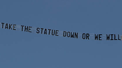 "A plane flying over the Penn State University campus in State College, pulls a banner reading ""Take the statue down or we will"" today."