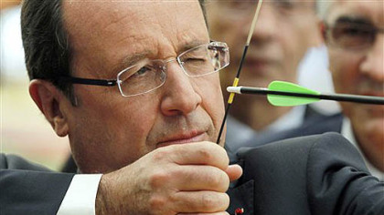 French President Francois Hollande aims as he prepares to shoot an arrow during a visit with members of the French Archery team for the London Olympics 2012, at their training headquarters in Paris, Monday, July 16, 2012.