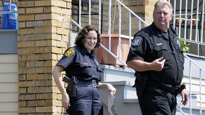 Pittsburgh police officers Christine Luffey, left, and Ray Kain leave a house in Carrick after checking on a call for a dog left out in the heat.