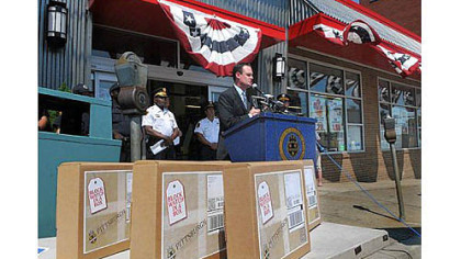 "Mayor Luke Ravenstahl speaks in front of the IGA in Beechview, with ""Block Watch in a Box"" boxes in the foreground."