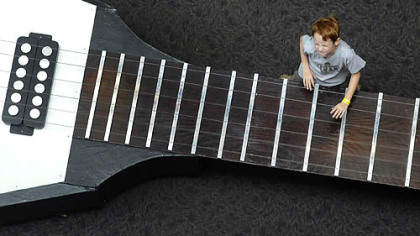 Nolan Casey, 8, of Harrison City jams on the Gibson Flying V guitar on display at the Carnegie Science Center on Tuesday.