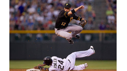 Pirates' Clint Barmes  jumps over a sliding Dexter Fowler after turning a double play in the third inning at Coors Field  in Denver, Colorado.