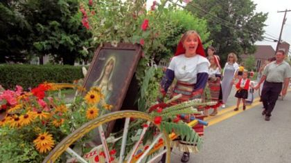 In 2000: Ashley Kessler responds to spectator cheering as she pushes a cart filled with flowers and a portrait of Our Lady of Mount Carmel as she and other parishioners march in the parade after Mass at St. Bartholomew Catholic Church, Crabtree, down the street and back.