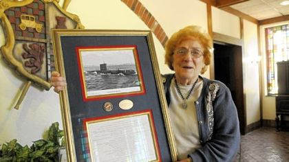 Natalie Carbone Mangini, who is manager of Carbone's Restaurant in Crabtree, also happens to have been a nuclear chemist for Westinghouse who worked on the atomic submarine Nautilus. She holds a picture of the sub and list of accomplistments presented to her.