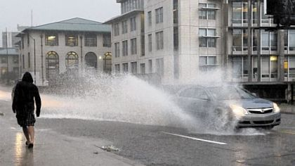 A vehicle creates a splash on Forbes Avenue near Carnigie Mellon University during an afternoon thunderstorm on Wednesday.