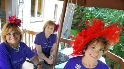 Members of a local chapter of the Red Hat Society, called the Glitz and Glamour Girls, are, from left, Donna Rotoloni, Mary Ann McCloskey and a local Red Hat &quot;Queen,&quot; Cathie Shenefelt, at Ms. Shenefelt&#039;s home in McMurray.