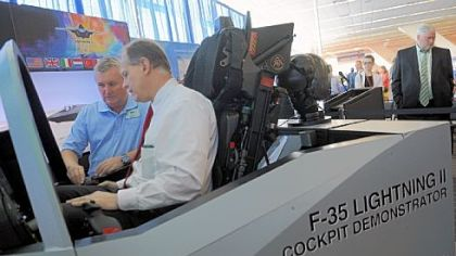 Flight instructor Tony Stutts, left, gives U.S. Rep. Mark Critz, D-Johnstown, a lesson in an F-35 flight simulator Monday at the National Association of Counties annual conference at the David L. Lawrence Convention Center.