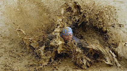 Mud runs pile on the slop as athletes move along a 5K course in which they slog their way through messy challenges.