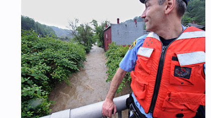 Pittsburgh paramedic Don Cunningham checks out the water level of the Streets Run Creek from Ramp Street in Hays.