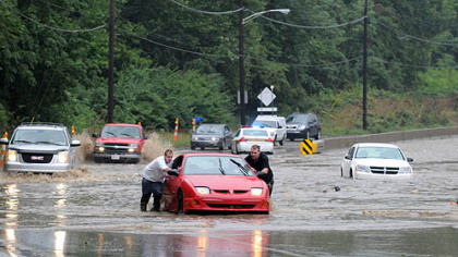 Jason Donahue, left, of Clairton and Dustin Tichenor of Bethel Park push their vehicle to safety after it was stranded in rising water on Route 51 near Bausman Street.