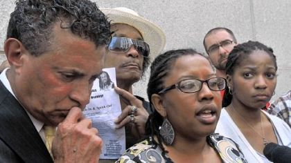 Kielan Miles, 18, right, the sister of Jordan Miles, and Tim Stevens, left, head of the Black Political Empowerment Project, listen outside the federal courthouse Thursday to Brandi Fisher, center, talk about Mr. Miles' testimony against the police officers who he said beat him.