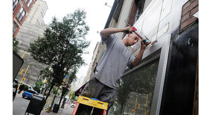 Dave Nemes, from Nemes Glass Corp., caulks windows Thursday next to the Penn Garrison. Construction and renovation projects are springing up all across the 800 and 900 blocks of Penn Avenue, Downtown.