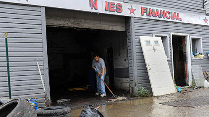 Rick Ibrahim sweeps out water Saturday from Best Auto Mart in the South Hills. There were several feet of water inside his store Friday after strong storms caused a flash flood.