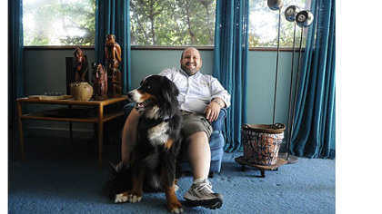 Homeowner Ed Pariser with his dog, Otto, in the home designed by Richard Neutra.