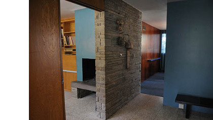 The front entry way has a polished terrazzo floor.  To the left is a den with a log-burning fireplace.