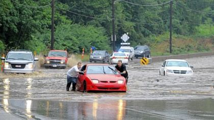 Jason Donahue, left, of Clairton and Dustin Tichenor of Bethel Park push their vehicle out of rising floodwaters on Route 51 near Bausman Street on Friday.