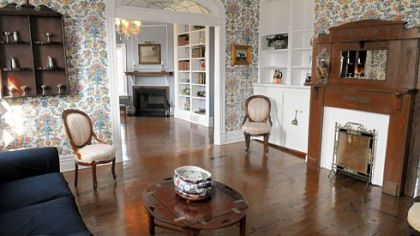 A parlor has a view into the living room, which has picture-frame molding and Wedgwood blue walls.