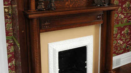 The decorative wooden mantlepiece and fireplace surround is highlighted with a mirror.