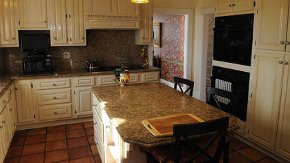 The updated kitchen features a cream-colored coffered ceiling and cabinetry, and red Mexican ceramic tile floors. A center island topped with Venetian Gold granite seats three.