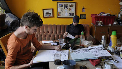 "Daniel McCloskey illustrates his comic, ""Top of the Line,"" while visiting writer Matt Whispers of Chicago works on his poems at the artist collective Cyberpunk Apocalypse."