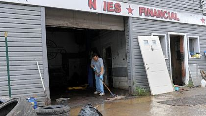 Rick Ibrahim sweeps out water from Best Auto Mart along Route 51 in the South Hills on Saturday after strong storms caused flash flooding Friday evening.