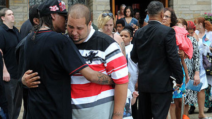 Ron Spence, left, of McKeesport comforts C.J. Sims following the funeral of his brother James Andre Lane Sims outside the New Beginnings Ministry church in McKeesport.
