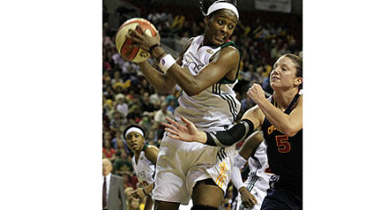 Seattle Storm's Swin Cash, left, grabs a rebound during a WNBA basketball game in 2011.