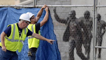 Workers place a tarp on a fence in front of the statue of former Penn State football coach Joe Paterno before removing it.