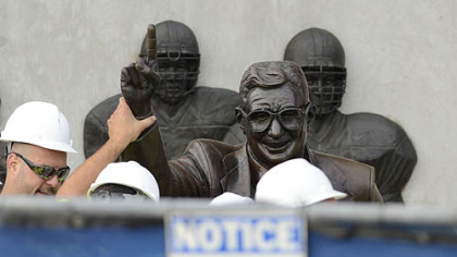 Workers handle the statue of former Penn State football coach Joe Paterno before removing it.
