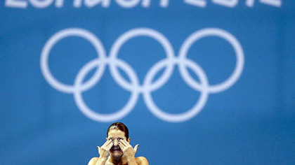 Brazilian diver Juliana Veloso wipes water from her eyes while training at the 2012 London Olympics, Sunday, July 22, 2012, in London.