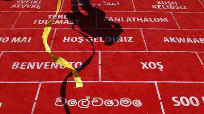 A performer walks on the carpet during the Olympic Team Welcome Ceremony at the Athletes' Village at the Olympic Park, Sunday, July 22, 2012, in London.