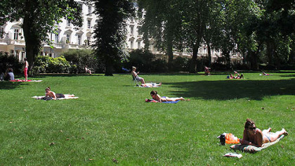 Sunbathers soak up rays in a southwest London park on Sunday, July 22, 2012. After weeks of unseasonably chilly temperatures, the sun has come out in the capital with less than a week to go until the start of the London Olympics.