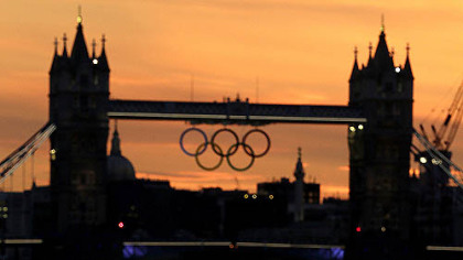 The sun sets behind London's landmark Tower Bridge with a display of Olympic rings in the distance on Saturday, July 21, 2012, in London. The 2012 London Olympics open this Friday.