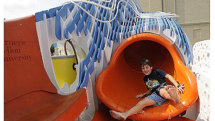 Seven-year-old Dylan Folan slides down the Puriflume, a 14-foot play contraption that filters and recirculates water, on Thursday. Students taught by Dylan's father, Carnegie Mellon University architecture professor John Folan, designed the feature with community input. The city will be looking at it for possible replication in future spray parks.