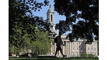 A Penn State University student walks in front of Old Main on campus. The school will learn its punishment from the NCAA today.